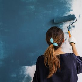 Woman Painting Wall Blue with Roller