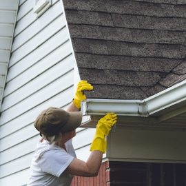 Woman Cleaning Gutters on Her House