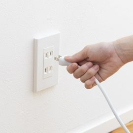 Hand Plugging in Cord in Outlet
